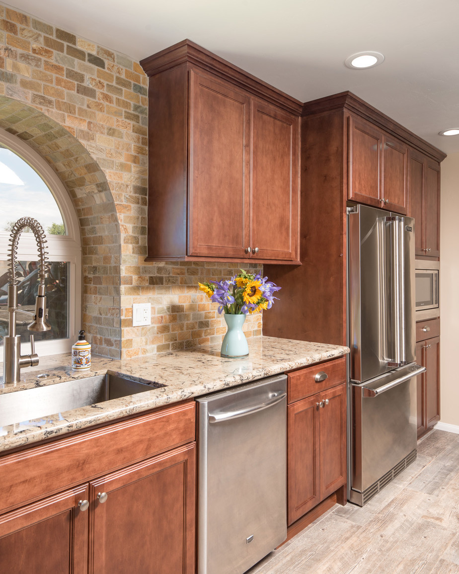 warm wood cabinets in a country style kitchen with full tile backsplash