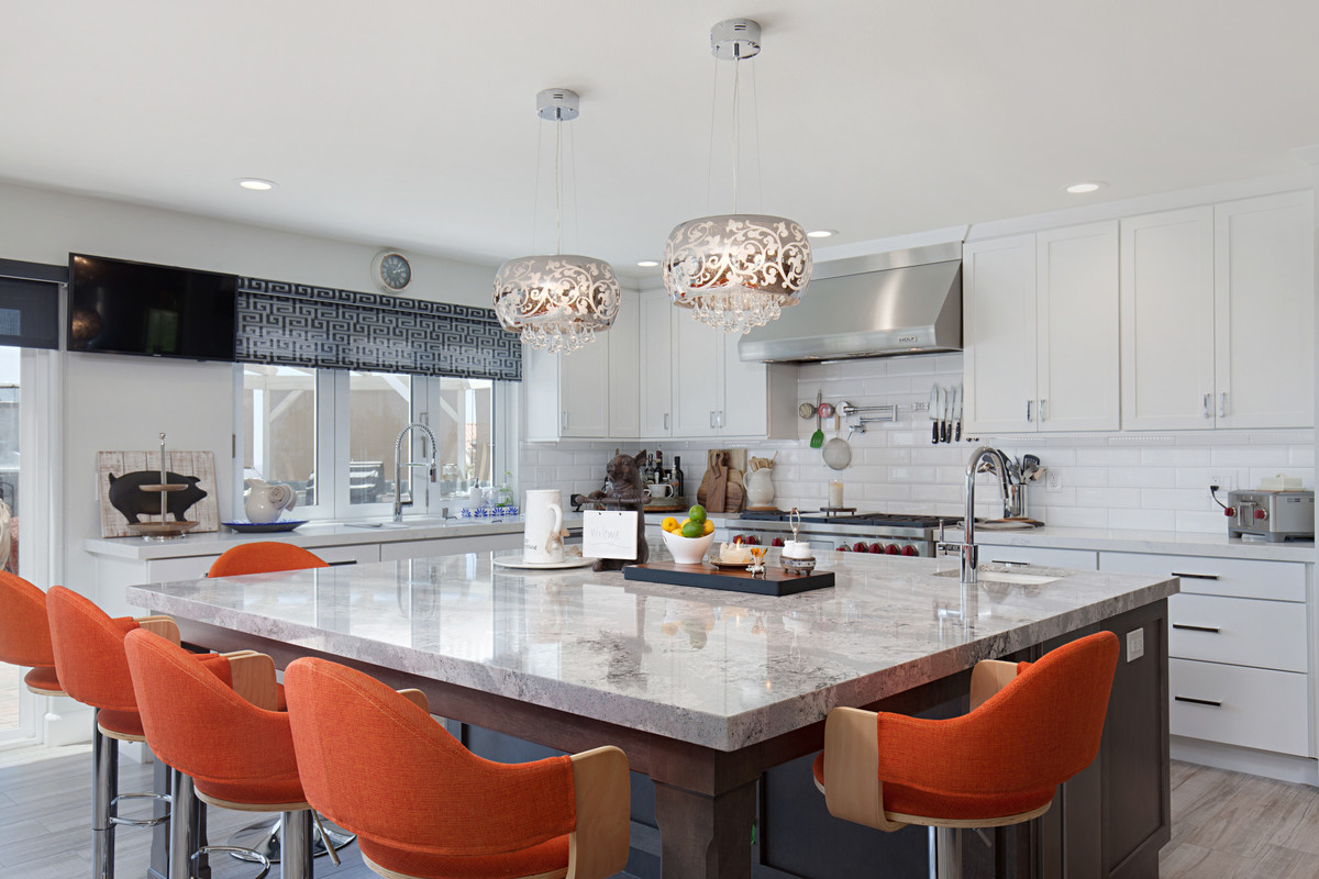 modern kitchen remodel with dual tone kitchen cabinets and bright orange chairs