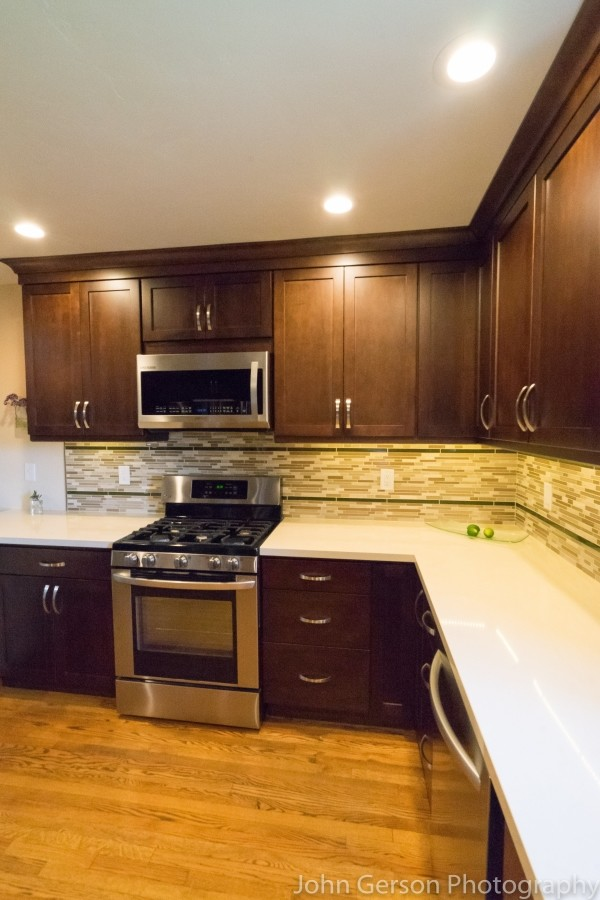 dark wood kitchen cabinets with neutral backsplash and light corian countertops
