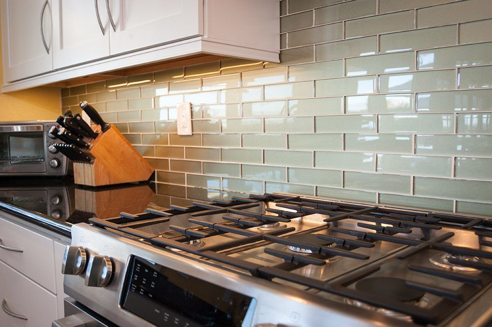 Close up photo of green subway tile backsplash against stainless steel appliances