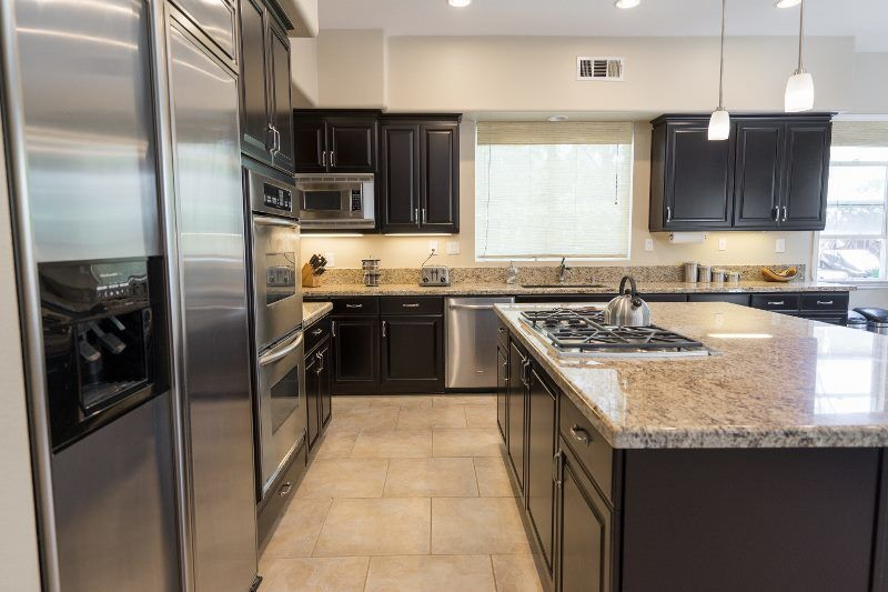dark wood kitchen cabinets with stainless steel appliances