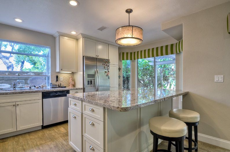 open concept kitchen remodel with white cabinets and granite countertops