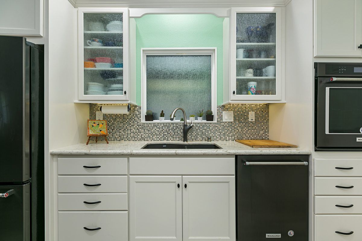 Kitchen remodel featuring glass front cabinets over sink area