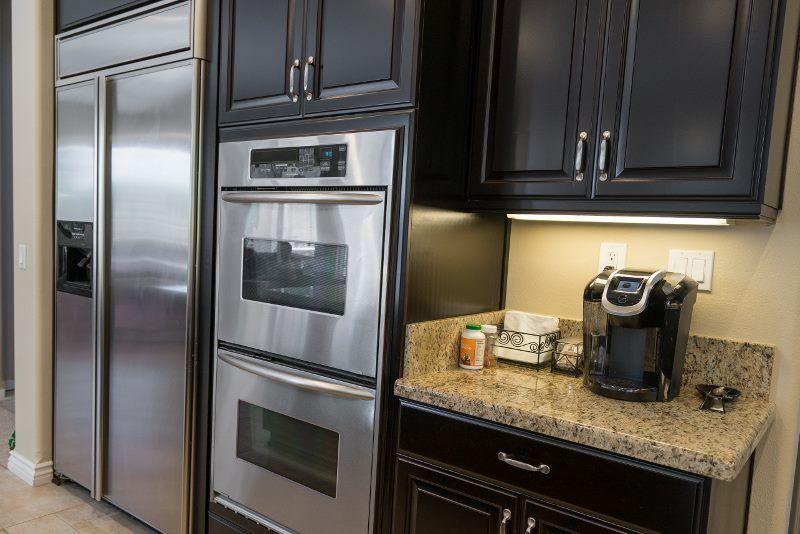 stainless steel kitchen appliances set in dark wood cabinets