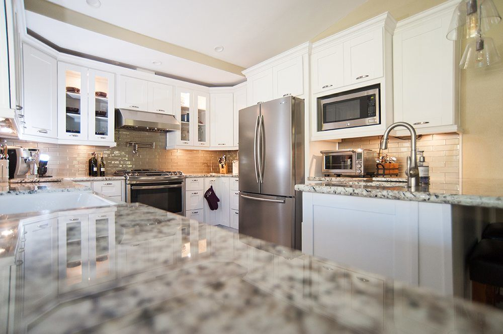 Small U Shaped Kitchen Remodel With White Cabinets and Stainless Steel Appliances
