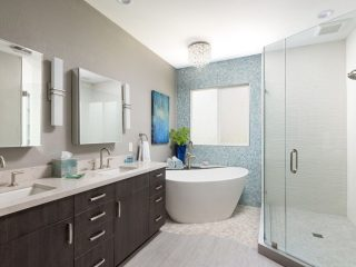 stunning modern bathroom remodel with dark cabinets and white free standing tub with blue wall tile floor to ceiling
