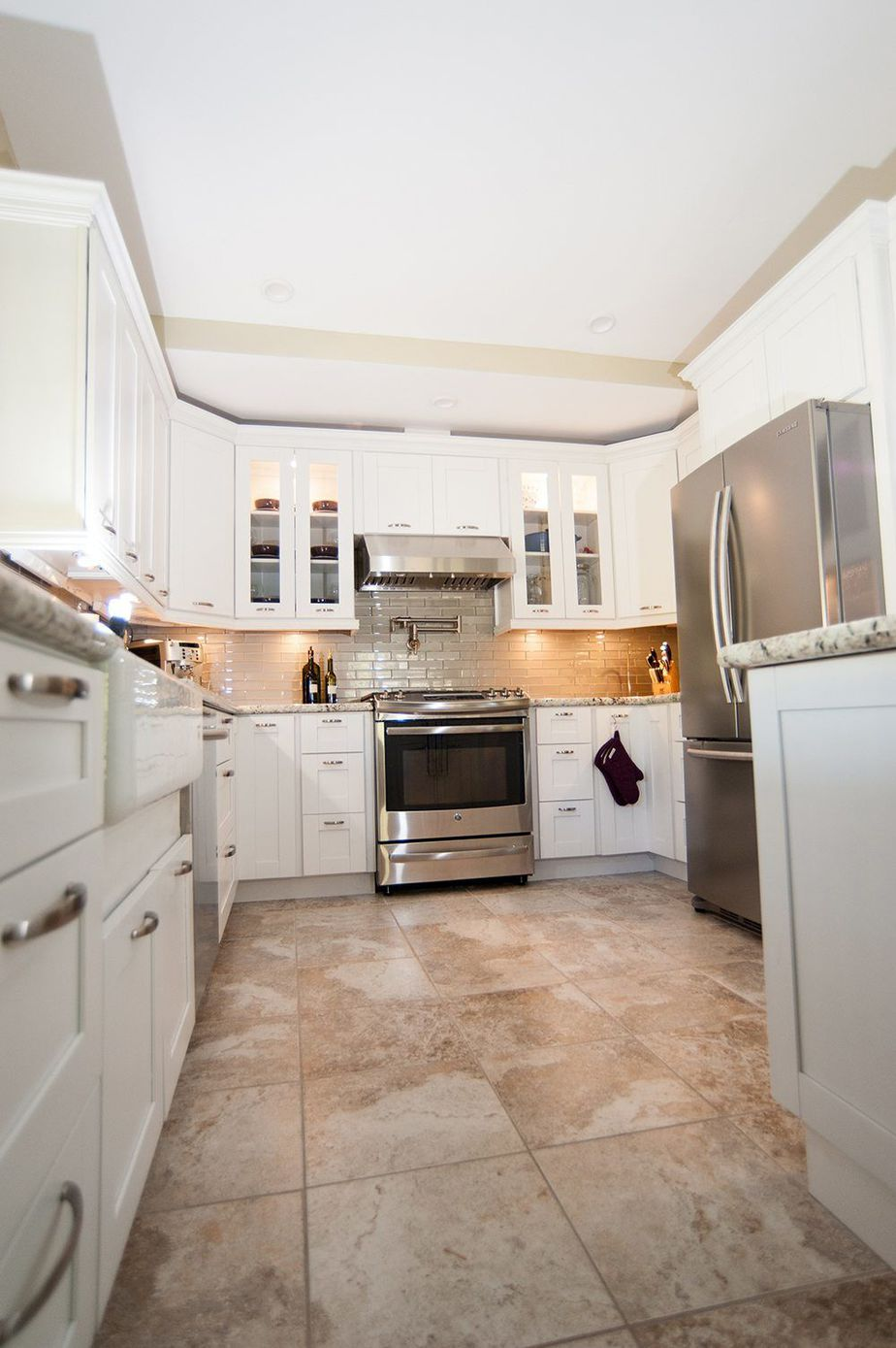 Kitchen Remodel With White Cabinets Featuring Glass Front Doors Near Stovetop