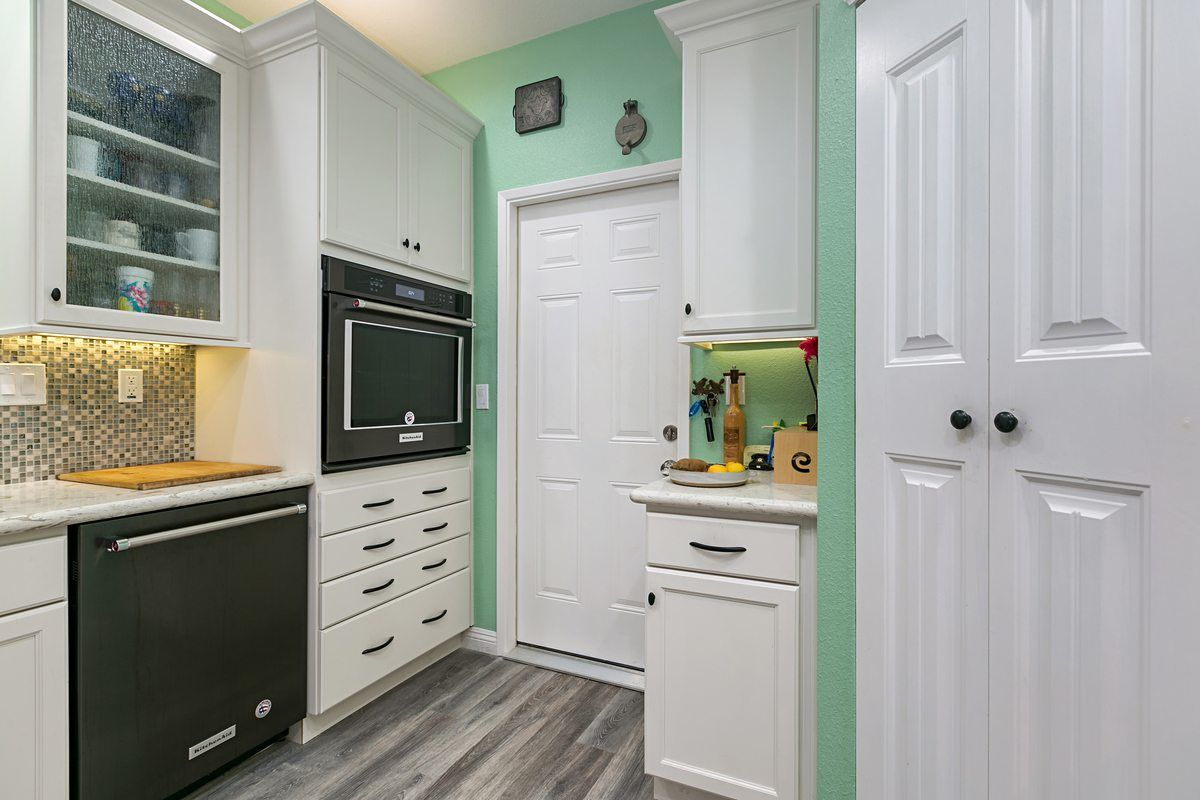 small kitchen remodel with white cabinets some with glass front doors