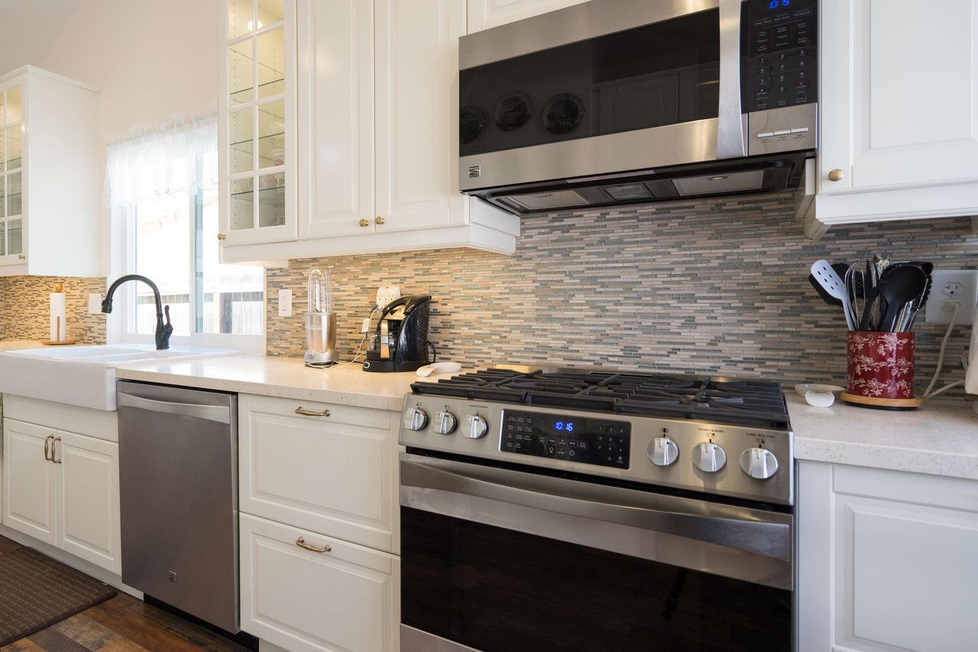 colorful grey and cream backsplash against white kitchen cabinets and countertops