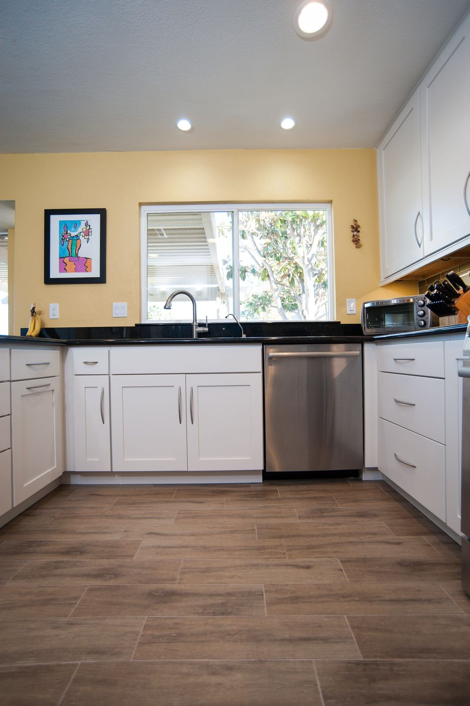 kitchen remodel featuring a tile floor that looks like wood against white starmark cabinetry and yellow painted walls