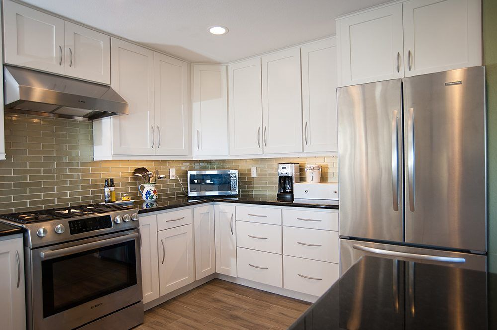 white kitchen cabinets with green subway tile backsplash and stainless steel appliances