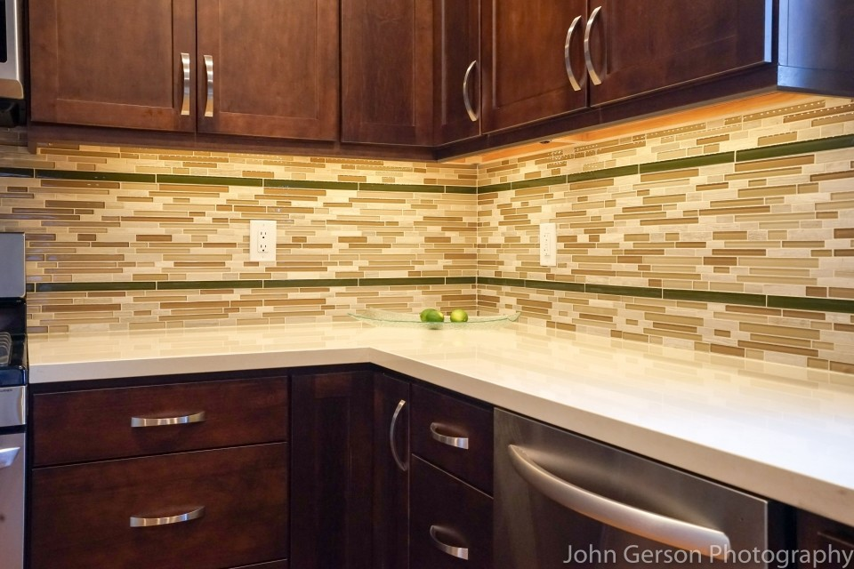 green and brown kitchen backsplash against dark wood kitchen cabinets and white corian countertops
