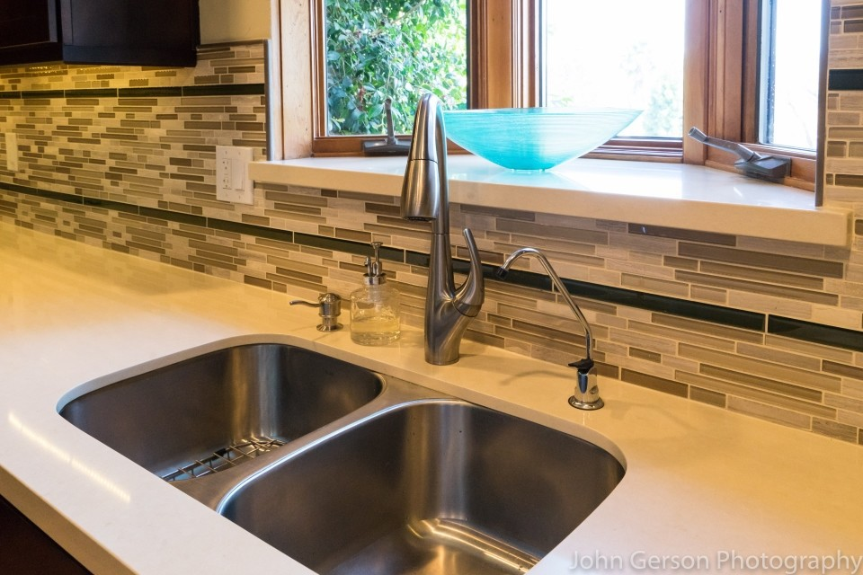 stainless steel kitchen sink and faucet with neutral tile backsplash