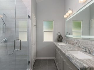 bathroom remodel in a grey color scheme with a lighted mirror