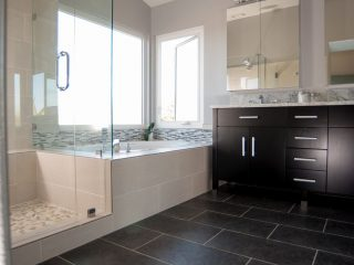 master bathroom remodel featuring dark cabinetry with light countertops