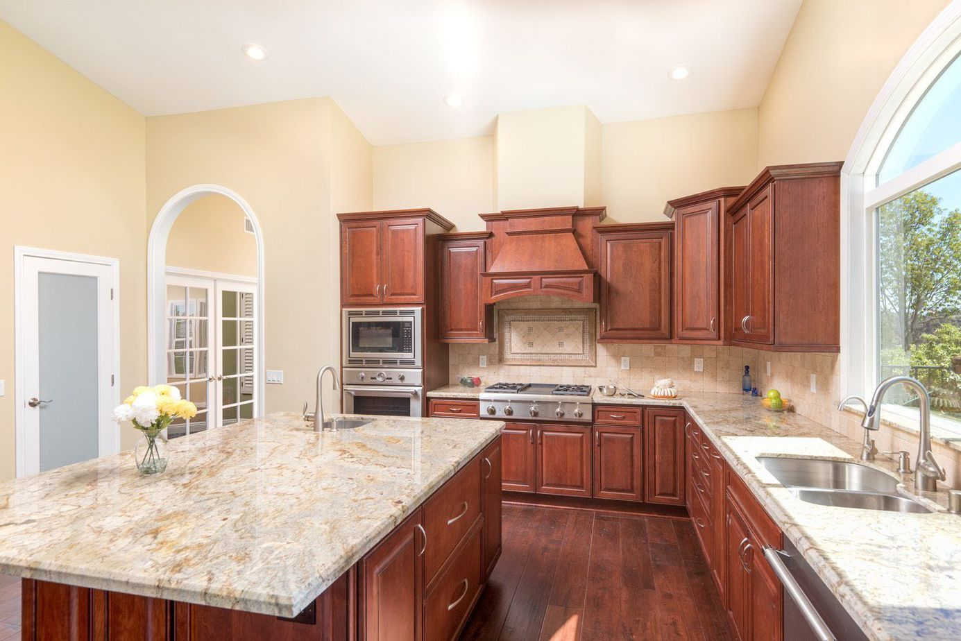 large kitchen remodel in scripps ranch with huge island including a bar sink and mosaic tile over cooktop