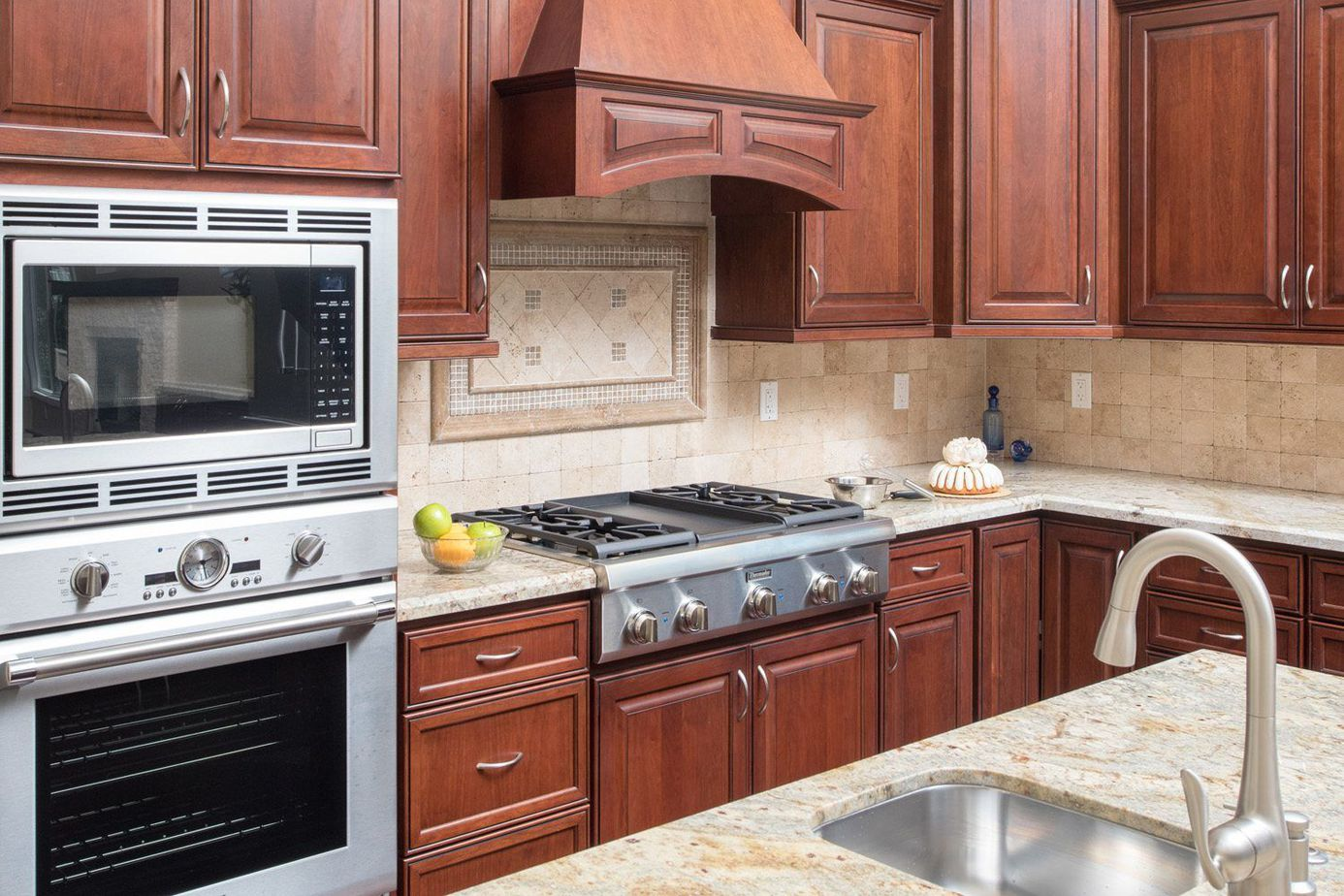 paprika colored kitchen cabinets with mosaic tile backsplash over the cooktop